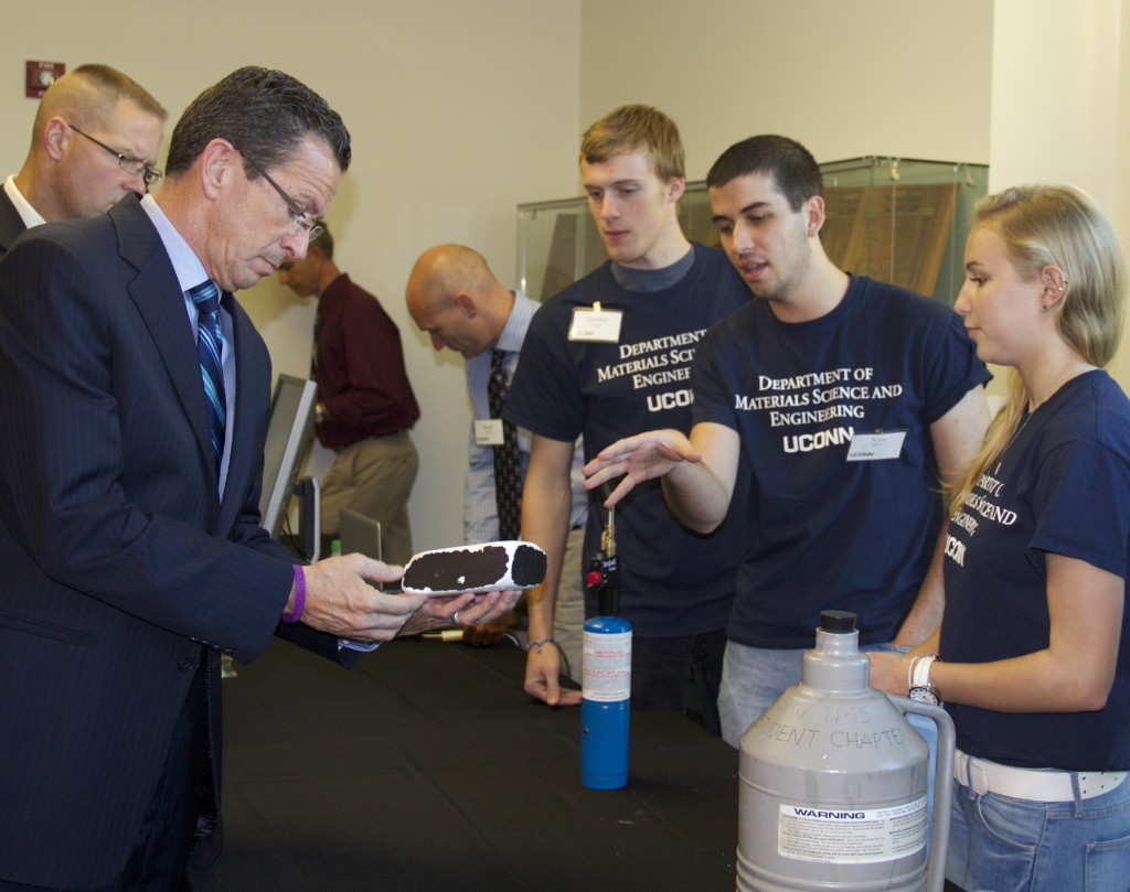 Rheanna Ward, Nathan Martin, Zachary Thatcher, showing Governor Dannel P. Malloy a ceramic foam space shuttle tile.