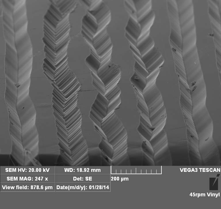 A scanning electron microscope image of a 45 rpm vinyl record from Doug's project in MSE 3056 investigating the storage density of analog vs. digital media.
