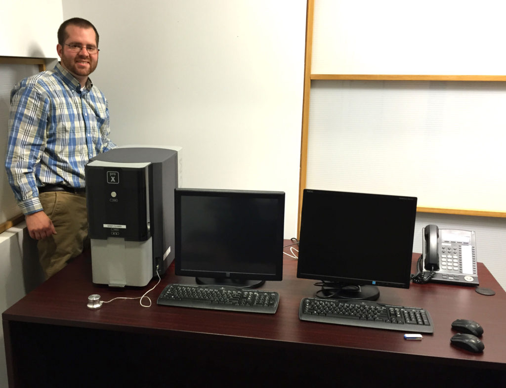 Neal Magdefrau, Ph.D., stands next to one of the desktop SEMs that his company, Electron Microscopy Innovative Technologies, LLC, rents out.