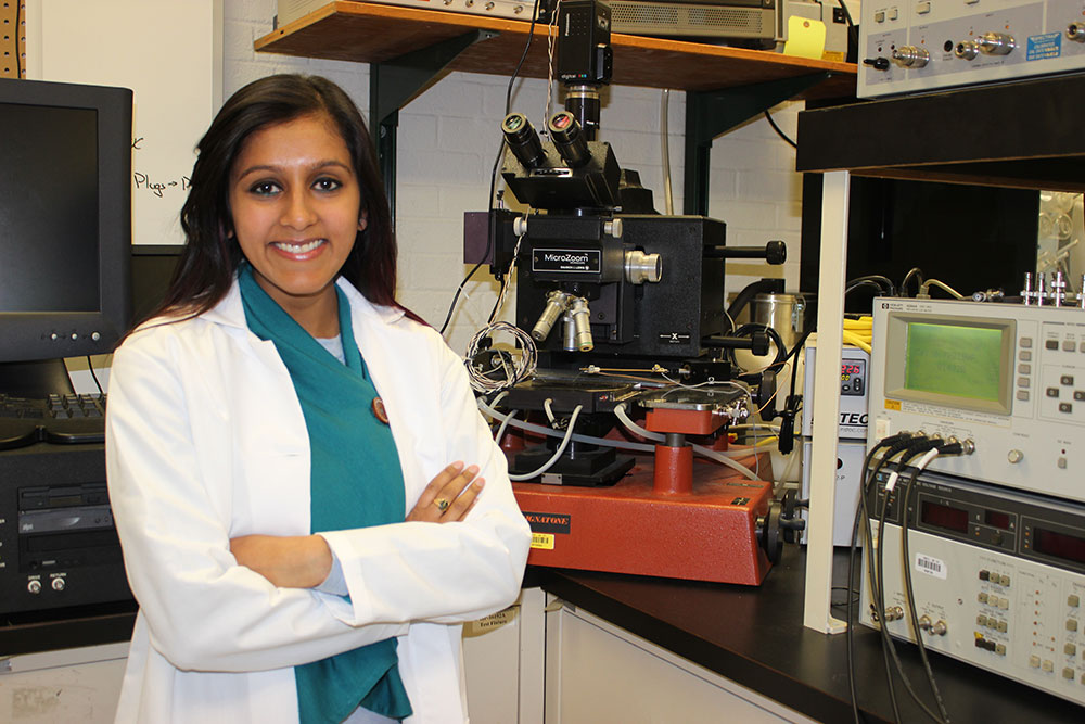 Tulsi Patel, Ph.D. student in Dr. Alpay's lab, stands beside a probe station connected to a ferroelectric test system that measures polarization-electric field (P-E) hysteresis loops.