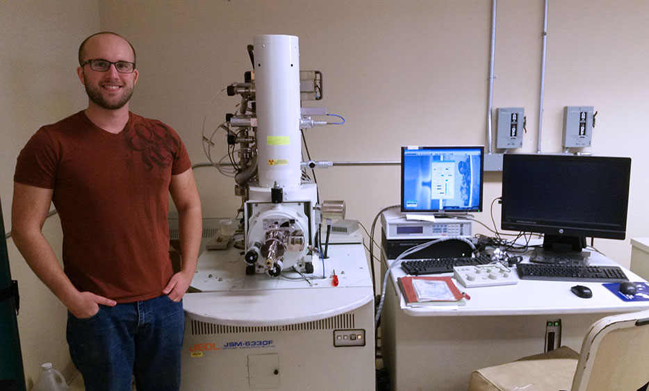 Tyler Flanagan with Field Emission Scanning Microscope, used to perform in-situ micropillar compression and tension.