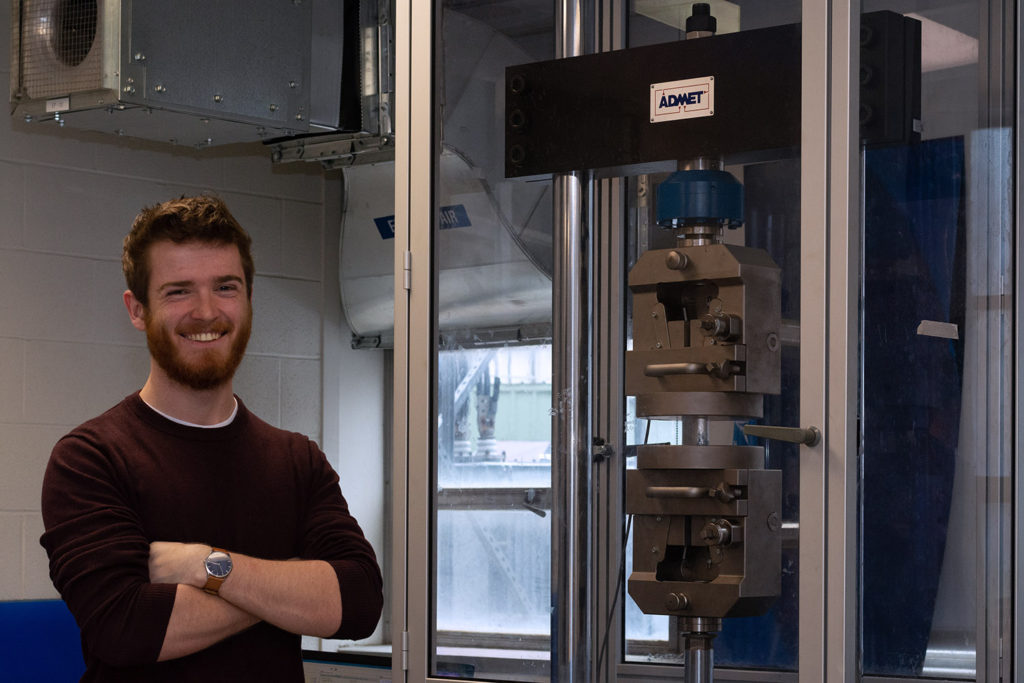 Joseph Podbielski next to a mechanical tester in Dr. Volkan Ortalan's lab, which is used for pressure and stress testing of materials