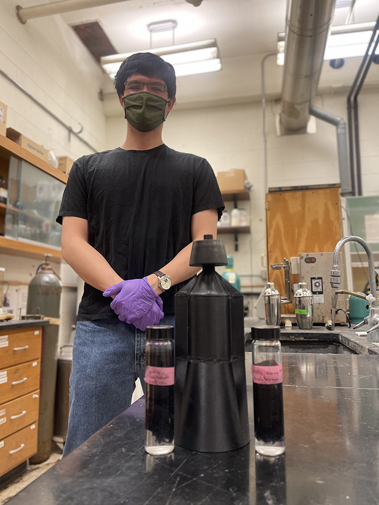Robert accompanied by his custom 3D printed Büchner funnel and two graphene-coated samples
