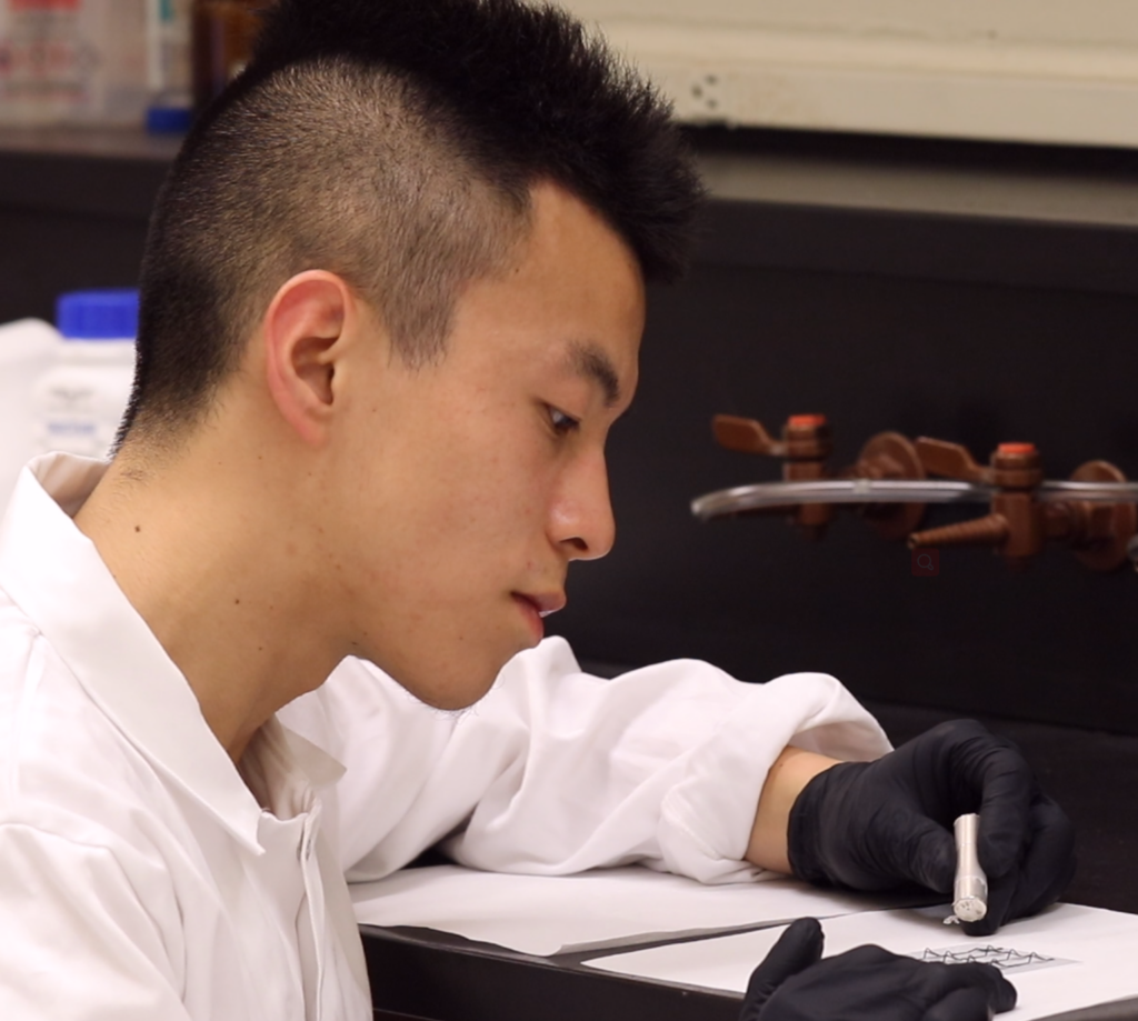 photo of Ph.D. student Yi Li, in Assistant Professor Wang's group is actuating multistable, origami-inspired structures using a portable magnet.